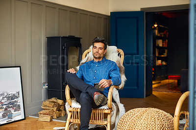Buy stock photo Shot of a young man using a digital tablet while relaxing on a rocking chair at home