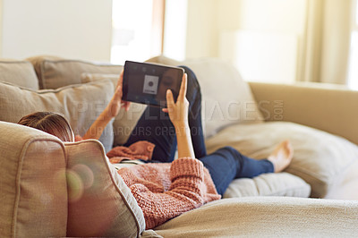 Buy stock photo Rearview shot of a young woman lying on her sofa watching a movie on a digital tablet