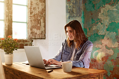 Buy stock photo Shot of a young woman working on her laptop at a desk in her room
