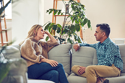 Buy stock photo Shot of an affectionate mature couple sitting on the sofa at home