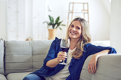 Buy stock photo Shot of an attractive and mature woman enjoying a glass of wine at home