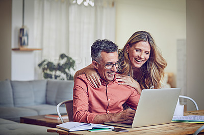 Buy stock photo Shot of a mature woman leaning on her husband while he works on his laptop