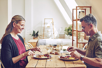 Buy stock photo Shot of an affectionate and mature couple enjoying a meal together