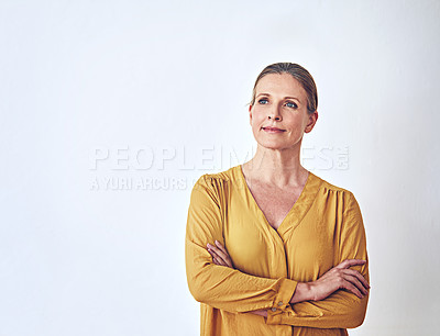 Buy stock photo Shot of an attractive and mature woman looking thoughtful against a grey background