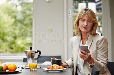 Buy stock photo Shot of a mature businesswoman using her phone while eating breakfast at home