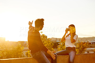 Buy stock photo Shot of a young woman taking a photo of her boyfriend