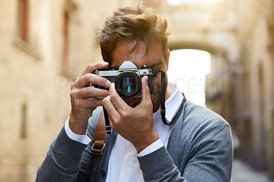 Buy stock photo Cropped shot of a stylish young male tourist taking photos of a foreign city