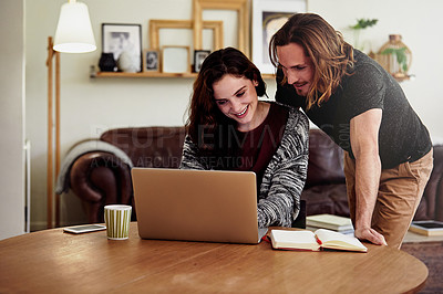 Buy stock photo Shot of a handsome young man watching his wife as she works from home