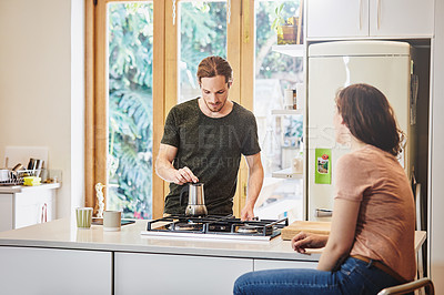 Buy stock photo Shot of a handsome young man preparing coffee in the kitchen while talking to his wife