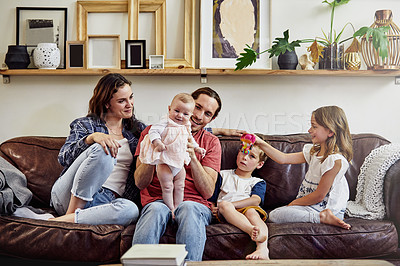 Buy stock photo Shot of a happy and loving young family sitting on the sofa at home