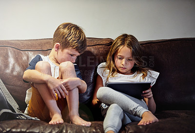 Buy stock photo Shot of a young girl reading to her brother while sitting on a sofa at home