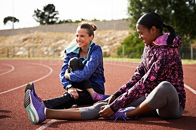 Buy stock photo Shot of two young athletic women warming up on the track before a run