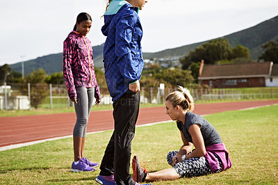 Buy stock photo Shot of an athletic young woman warming up on the track before a run
