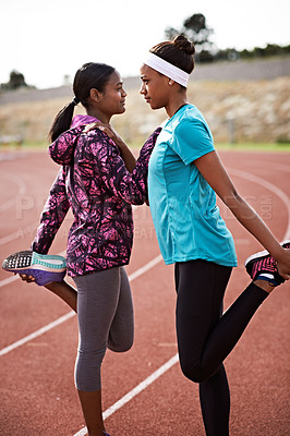 Buy stock photo Shot of two young athletic young women warming up face to face on the track