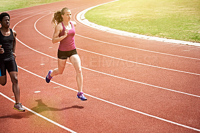 Buy stock photo High angle shot of two young athletic women running on the track