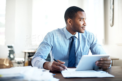Buy stock photo Cropped shot of a handsome young businessman working on a digital tablet in an office