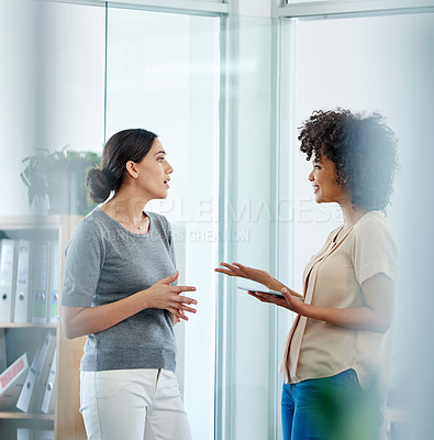 Buy stock photo Shot of two female colleagues having a discussion in their office