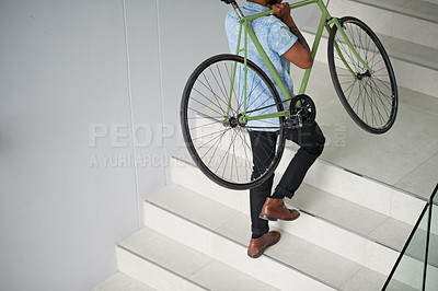 Buy stock photo Shot of an unrecognisable designer carrying his bicycle up a staircase in an office