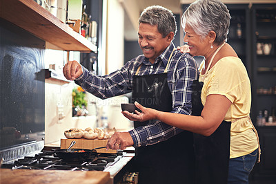 Buy stock photo Shot of a mature couple cooking together at home