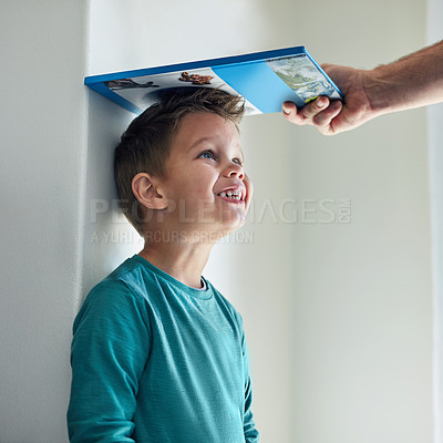Buy stock photo Cropped shot of a little boy getting his height measured against a wall with a book