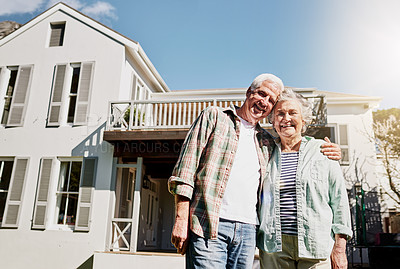 Buy stock photo Shot of a happy senior couple standing together in front of their house