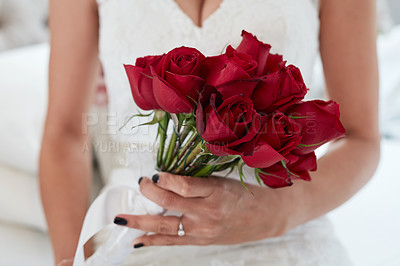Buy stock photo Cropped closeup of a woman holding red roses on her wedding day