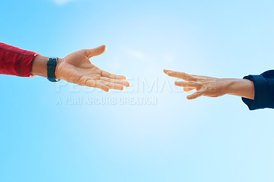 Buy stock photo Shot of two unidentifiable hikers reaching for each other's hands against a clear blue sky