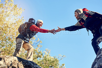 Buy stock photo Shot of a pair of happy hikers reaching for each other's hands on a mountain trail