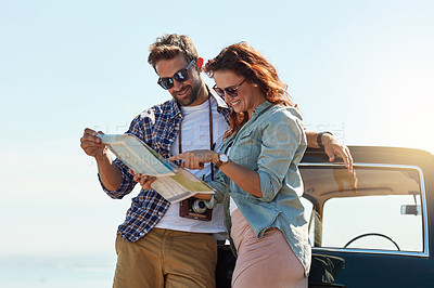 Buy stock photo Cropped shot of an affectionate couple looking at a map while enjoying a roadtrip