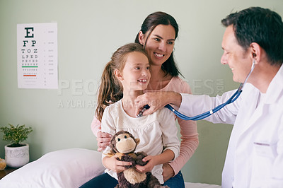 Buy stock photo Shot of a male doctor checking his young patient's heart rate
