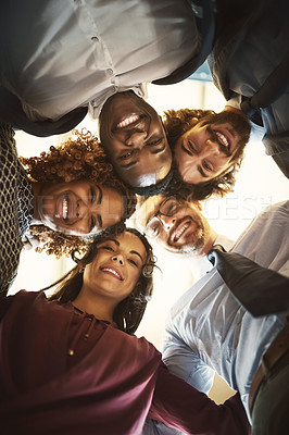Buy stock photo Low angle portrait of a team of happy businesspeople putting their heads together in a huddle