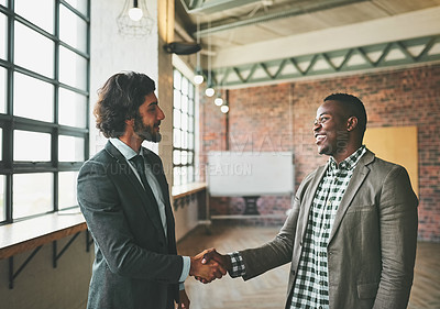 Buy stock photo Shot of two happy businessmen shaking hands in the office