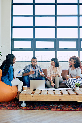 Buy stock photo Shot of a group of colleagues using a laptop together in a modern office