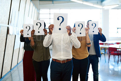 Buy stock photo Shot of a group of businesspeople holding up placards with question marks on it