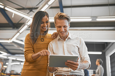 Buy stock photo Cropped shot of two young businesspeople looking at a tablet in their office