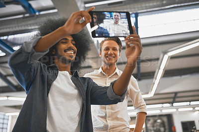 Buy stock photo Cropped shot of two young businessmen taking a selfie with a tablet in their office