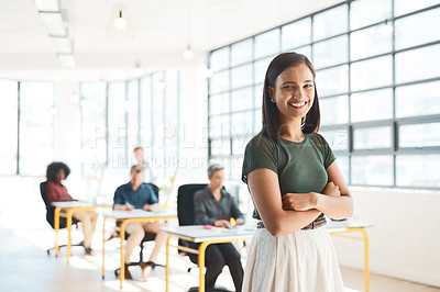 Buy stock photo Portrait of a happy designer posing in the office while her colleagues work in the background
