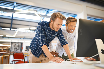 Buy stock photo Cropped shot of two young male designers working on a desktop in their office