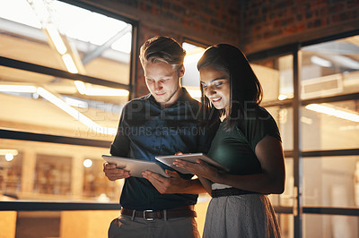Buy stock photo Shot of two designers using their digital tablets while working nightshift