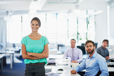 Buy stock photo Portrait of an attractive young businesswoman standing in an office with her colleagues in the background