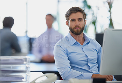 Buy stock photo Portrait of a handsome young businessman sitting in an office with his colleagues in the background