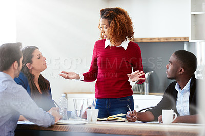 Buy stock photo Shot of an attractive young businesswoman addressing her team during a meeting
