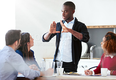 Buy stock photo Shot of a handsome young businessman addressing his team during a meeting