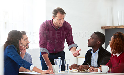 Buy stock photo Shot of a handsome mature businessman addressing his team during a meeting