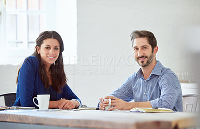 Buy stock photo Cropped portrait of two young businesspeople sitting at a table in the office