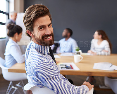 Buy stock photo Cropped portrait of a handsome young businessman sitting in the boardroom during a meeting