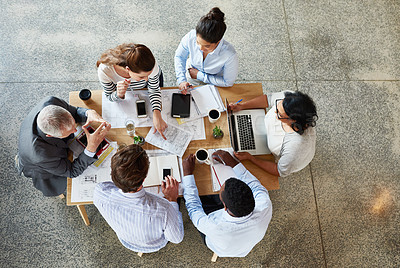 Buy stock photo High angle shot of a group of businesspeople working while sitting around in a table