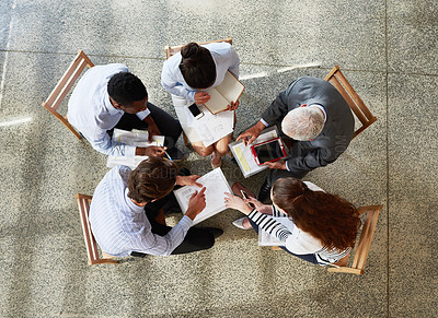 Buy stock photo High angle shot of a group of businesspeople working while sitting around in a circle