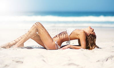 Buy stock photo Shot of a sexy young woman lying on the beach in a bikini