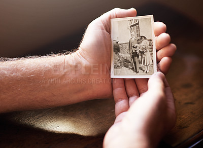 Buy stock photo Cropped shot a man holding an old black and white photograph of himself and his wife